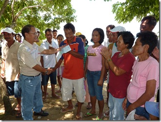 AQD's Mr. Renato Agbayani hands over a check to the officers of a fisherfolk organization in San Antonio