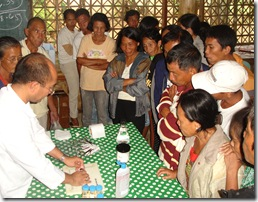 Dr. Edgar Amar (leftmost) demonstrates on the disease diagnosis. Right: Fisherfolk  take turns glancing into a microscope