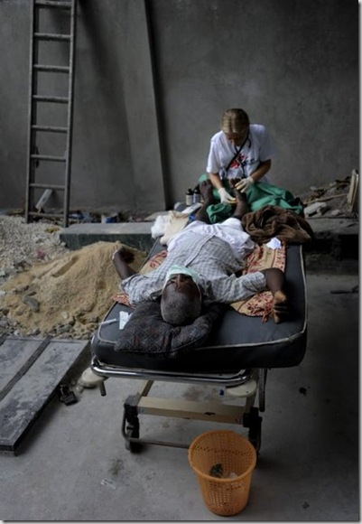 Doctors Without Borders surgeon in #Haiti treats a man with a boken foot in a makeshift surgery room outside of the hospital. © Julie Remy