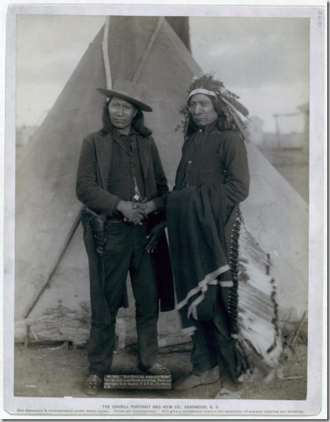 "Title: ""Red Cloud and American Horse."" The two most noted chiefs now living Two Oglala chiefs, American Horse (wearing western clothing and gun-in-holster) and Red Cloud (wearing headdress), full-length portrait, facing front, shaking hands in front of tipi--probably on or near Pine Ridge Reservation. 1891. Repository: Library of Congress Prints and Photographs Division Washington, D.C. 20540"