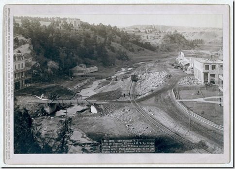"Title: ""Hot Springs, S.D."" From the Fremont, Elkhorn and M.V. Ry. bridge looking north to Fred T. Evans residence and plunge bath Bird's-eye view of a developing small town with railroad track running through it. Large buildings on hilltops in background. 1891. Repository: Library of Congress Prints and Photographs Division Washington, D.C. 20540"