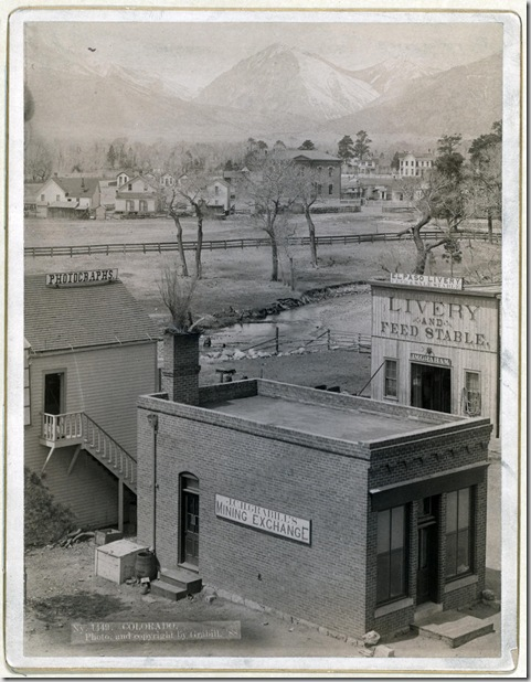 Title: Colorado Three buildings with signs reading: Grabill's Mining Exchange, Photographs, and El Paso Livery; river and houses in middleground; mountains in background. 1888. Repository: Library of Congress Prints and Photographs Division Washington, D.C. 20540