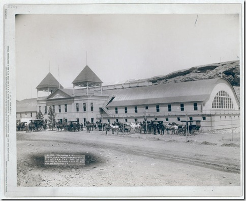 "Title: ""Hot Springs, S.D."" Exterior view of largest plunge bath house in U.S. on F.E. and M.V. R'y Large building with several horses and carriages in front. 1891. Repository: Library of Congress Prints and Photographs Division Washington, D.C. 20540"