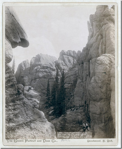 "Title: ""Lake Harney Peaks,"" near Custer City, S.D., on B. & M. Ry Close view of peaks; hikers sitting and standing on ridges. 1891. Repository: Library of Congress Prints and Photographs Division Washington, D.C. 20540"