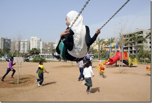 CHILDREN AND PARENTS PLAYING IN A PARK IN TRIPOLI, LEBANON Photograph by Julio Etchart www.julioetchart.com