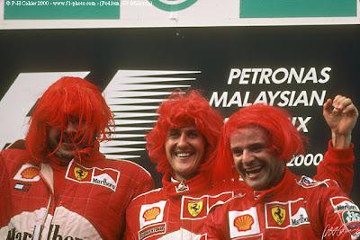 Росс Браун, Михаэль Шумахер и Рубенс Баррикелло в красных париках на подиуме Гран-при Малайзии 2000