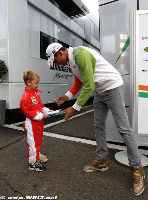 Адриан Сутиль дает автограф мальчику в комбезе Ferrari на Гран-при Бельгии 2010