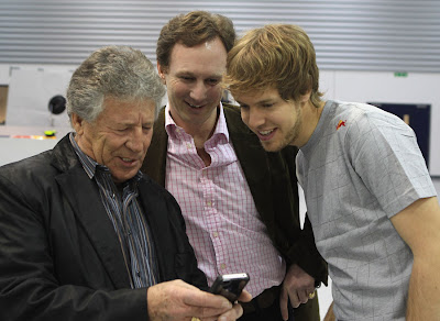 Марио Андретти показывает Себастьяну Феттелю и Кристиану Хорнеру что-то на телефоне