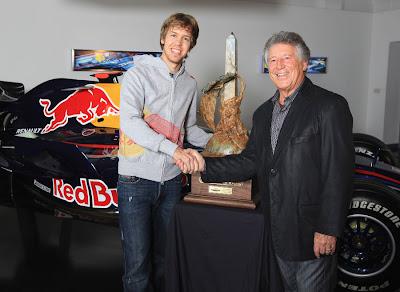 Себастьян Феттель и Марио Андретти на фоне кубка и болида Red Bull