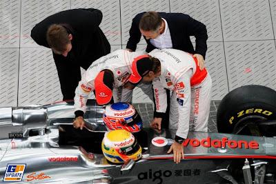 Льюис Хэмилтон и Дженсон Баттон на презентации McLaren MP4-26 ищут что-то в кокпите