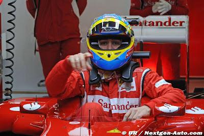 Фернандо Алонсо вылазит из кокпита Ferrari и показывает палецем на что-то тесты 2011 в Барселоне