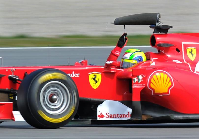 Фелипе Масса держит отваливающеюся антенну Ferrari на предсезонных тестах 2011 в Барселоне 9 марта 2011