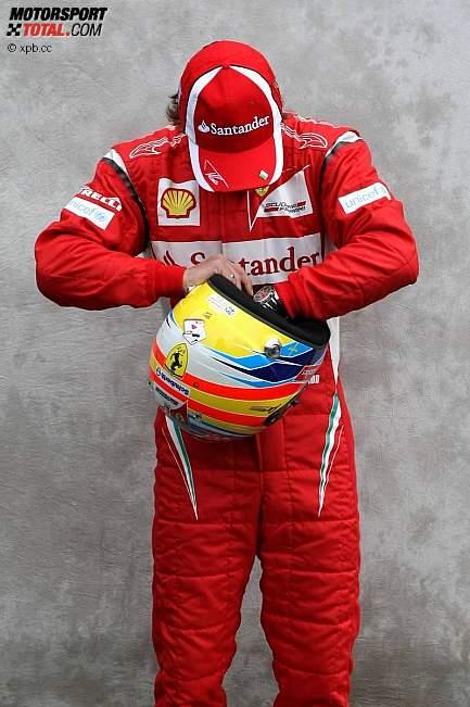 Фернандо Алонсо на фотосессии Гран-при Австралии 2011 ищет что-то в шлеме