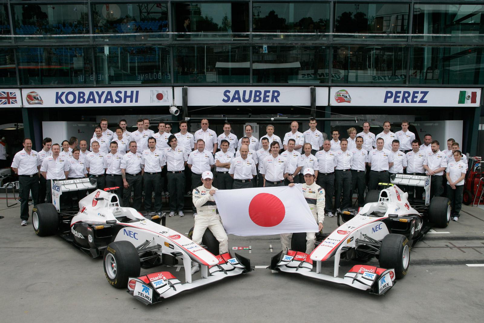 вся команда Sauber на фоне боксов с японским флагом на Гран-при Австралии 2011