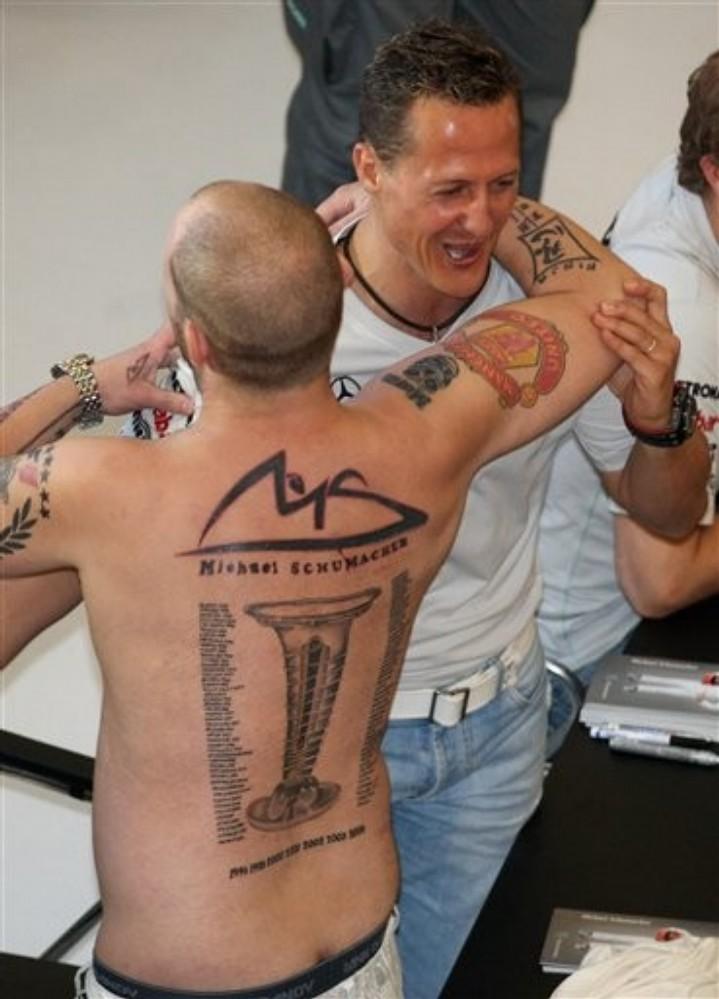 Михаэль Шумахер обнимается с болельщиком с татуировкой со всеми победами 7ми кратного чемпиона на автограф-сессии перед Гран-при Малайзии 2011