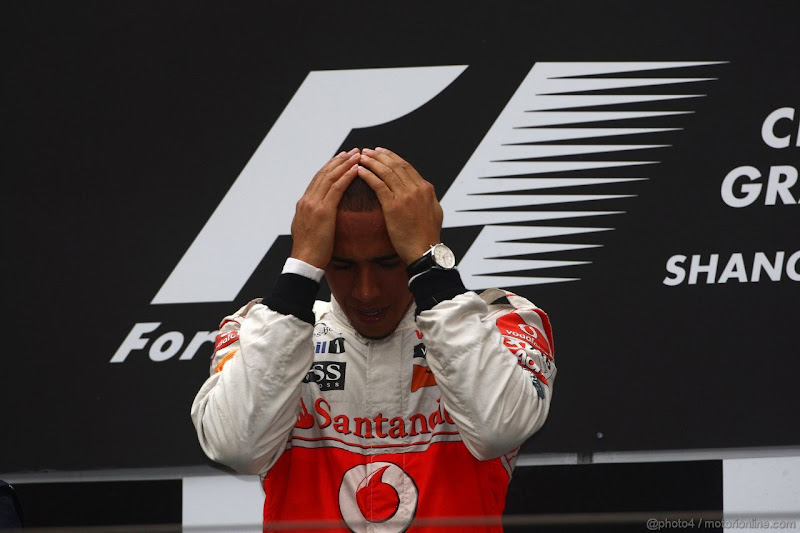 Льюис Хэмилтон на подиуме Гран-при Китая 2011 держится за голову