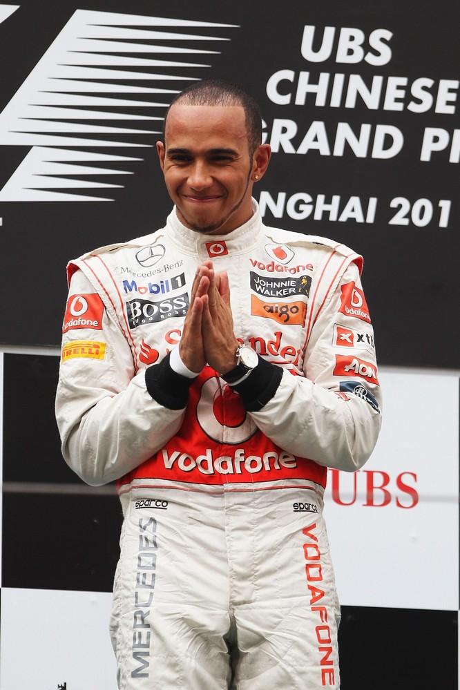 Льюис Хэмилтон потирает руки на подиуме после победы на Гран-при Китая 2011