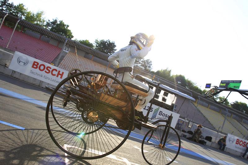 Нико Росберг едет по пит-лейну Хоккенхаймринга за рулем Benz Patentwagen 1886