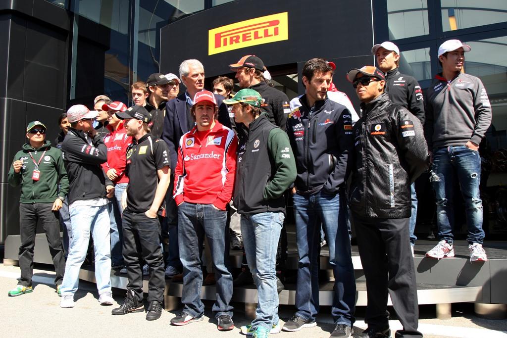 Пилоты Формулы-1 разговаривают на фотосессии на фоне моторхоума Pirelli на Гран-при Турции 2011
