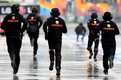 механики McLaren бегут по дождливому пит-лейну Истамбул-Парка на Гран-при Турции 2011