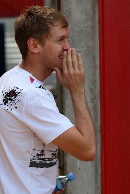 Себастьян Феттель прикрывает рот рукой и что-то шепчет на Гран-при Испании 2011