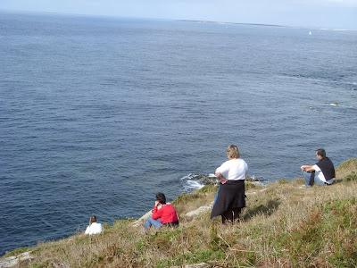 岬のふちに座って海を眺める人々