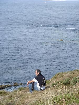 岬のふちに座って海を眺める人