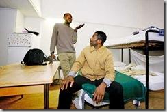 © PASCAL FRAUTSCHI | En Suisse depuis seulement quelques mois, Daniel Agu (à g.) et Jonathan Anthony disent avoir fui des rafles policières au Nigeria. Les deux requérants dorment dans un dortoir improvisé avec 14 autres personnes. Ils déplorent la surfréquentation du centre d'Anières, la promiscuité et le manque d'hygiène qu'elle implique, mais restent optimistes. ANIÈRES, LE 8 JANVIER 2009