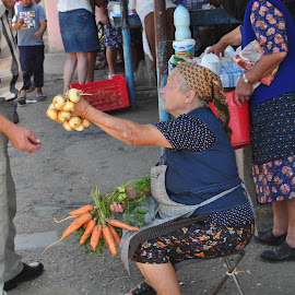 Offering Onions to Buy by Mike DeLong - City,  Street & Park  Markets & Shops ( onions, street, carrots, romania, marketplace,  )