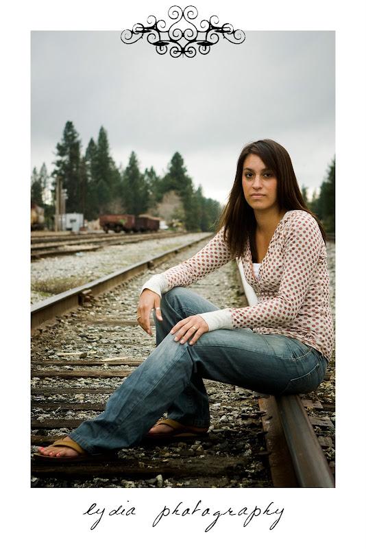 Senior girl sitting on railroad tracks at Simpson senior lifestyle Empire Mine portraits in Colfax, California