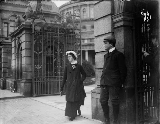 Young woman at the gate of Leinster House. The National Library of Ireland is visible behind her.