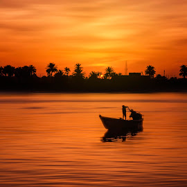 Fishing under the Sunset by Ehab Monther - Landscapes Waterscapes ( orange, 7100, sky, warm, seascape, fishing, nikon, landscape, fisherman, boat, golden )