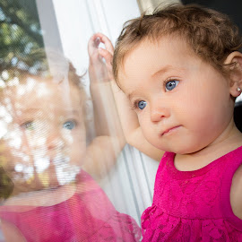 Reflecting by Mike DeMicco - Babies & Children Toddlers ( face, reflection, beautiful, cute, portrait, eyes, kid, hand, child, blonde, curly, girl, window, blue, baby, small )