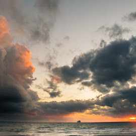 Sunrise in stormy weather by Fotografia Eva Stachova - Landscapes Underwater ( orange, clouds and sea, sea, seascape, boat, rainy clouds, morning, rough, cloud formations, sky, color, blue, cloud, weather, grey, sunrise, heavy clouds,  )