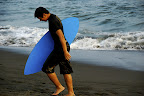 Japanese skimboarder with a blue board at Hiratsuka