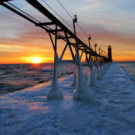 Grand Haven Pier at sunset by Kimberly Peterson - City,  Street & Park  Skylines ( michigan, grand haven, lake michigan, winter, catwalk, sunset, ice, lighthouse, horizon )