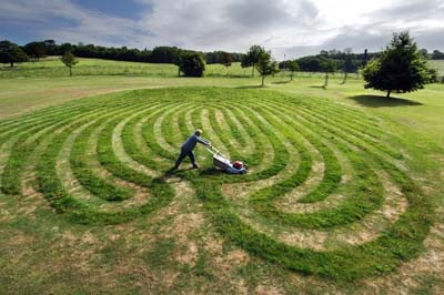 Picture by Roger Bamber : 25 June 2005: Park Art... Artist Chris Drury mows his