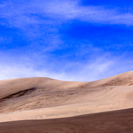 Solitude and sand by Steve Outing - Landscapes Deserts ( clouds, sand, lone hiker, hiker, colorado, solitude, shadows, panorama, sand dunes national park, wilderness, sky, nature, sand dunes,  )