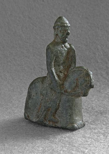 Although this object is likened to the Lewis chess-knights it may have actually been fixed to a larger object. Both the Lewis chessmen and this knight reflect the style of arms and armour used in the 11th century, though probably date to the 12th century. The Carlton-in-Lindrick knight was found by a metal-detectorist in 2004 and recorded by the Portable Antiquities Scheme.