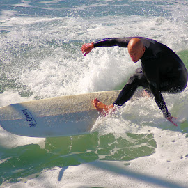 Dragging his hand in the water by Gary Mergelkamp - Sports & Fitness Surfing ( expert, surfer, action, wave, sport, ocean )