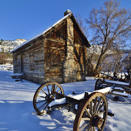 Simpler Times by David Knowles - Buildings & Architecture Homes ( cabin, old, wheel, wood, pioneer, wheels, wagon, old time, small house, stone chimney, rustic, shadows, rural, photography, historic, american pioneer, winter scene, frame, farmer, utah, snow, scene, wood cabin, chimney, antique )