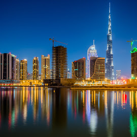 Dubai Skyline 2 by Cesar Crusat - City,  Street & Park  Skylines ( emirates, reflection, skyline, cityscape, travel, business, towers, city view, dubai, puente, long exposure, nikon, downtown, helicopter, office, building, larga exposicion, vivid colors, lake, skycrapers, burj khalifa, lago, d7100, uae, bridge, travel photography )