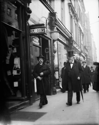 Two well-dressed gentlemen outside a tobacconist's shop