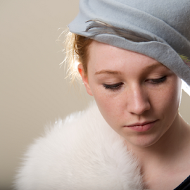 Close-up of redhead in fur looking down by Nick Dale - People Fashion ( girl, felt, blue, woman, fur, redhead, feathers, close-up, portrait, hat )