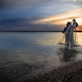 The Fisherman by Bouras Panagiotis - Landscapes Beaches ( clouds, blue sky, sky, sunset, gold time, greece, sea, seascape, net, fisherman, light, sun )