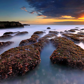 Rock Mengening Beach by Yudik Pradnyana - Landscapes Caves & Formations ( clouds, bali, sunset, long exposure, rock formation, landscapes, sun )