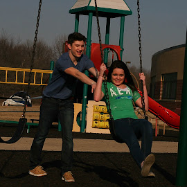 Swing by Delaney Franke - City,  Street & Park  City Parks ( film, happy, couple, swing, push )