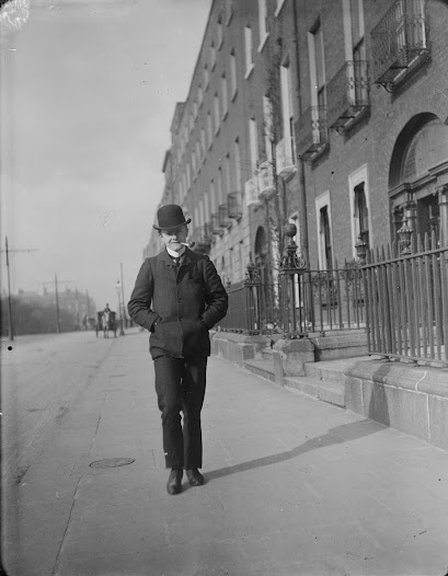Young man walking and smoking a pipe on Merrion Square.