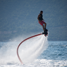 Flyboarder in pink shorts spiralling over spray by Nick Dale - Sports & Fitness Watersports ( water, hose, flyboarder, watersports, spray, waves, turkey, spiral, bodrum, jet )