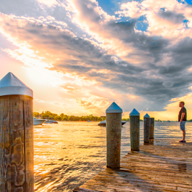 On The Pier by Bill Tiepelman - City,  Street & Park  Street Scenes ( clouds, water, minnesota, lake minnetonka, pier, dock )